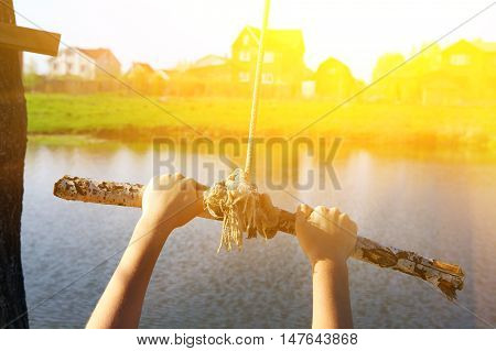 kids hands hold stick on swing rope close up photo on summer lake background ready to jump