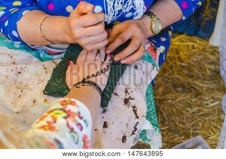 Unrecognizable woman applying henna on woman's hand to make mehndi. traditional body art