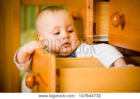 Baby opening drawer with clothes on wooden furniture - home interior