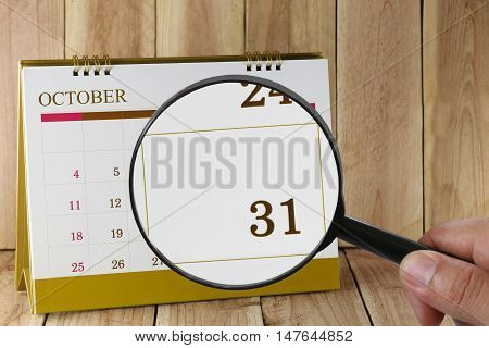 Magnifying glass in hand on calendar you can look thirty-one date of monthFocus number thirty one in OctoberConcept in business and meetings.