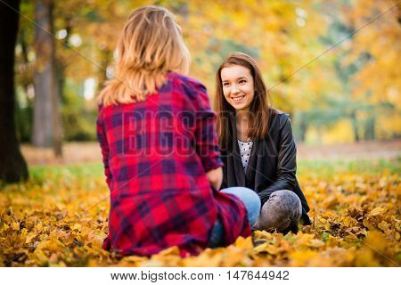Two friends -  teenage girls talking outdoor in autumn - sitting on ground in leaves