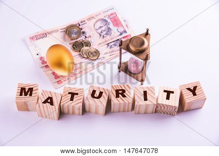 indian currency notes and coins with gold egg, sand clock and wooden blocks with word MATURITY written over it
