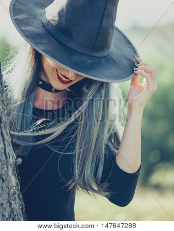 Scary young witch in a hat smiling outdoor. Theme of Halloween and magic