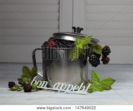blackberry in a metall mug with a cover on a table and an inscription bon appetite