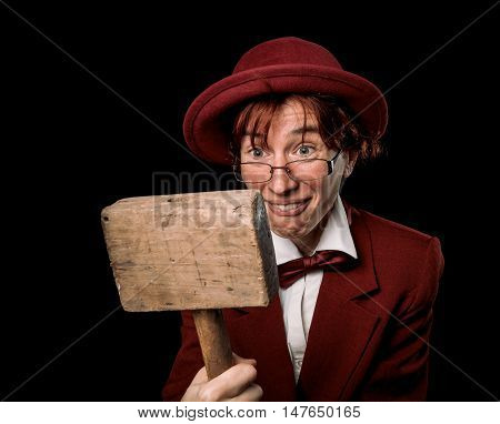 Strange person in a suit and bowler  looking at wooden hammer in astonishment. Color toning