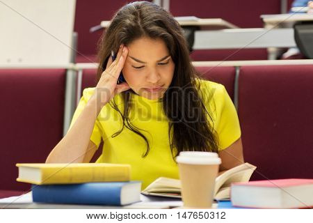 education, high school, university, learning and people concept - bored student girl with books and coffee on lecture