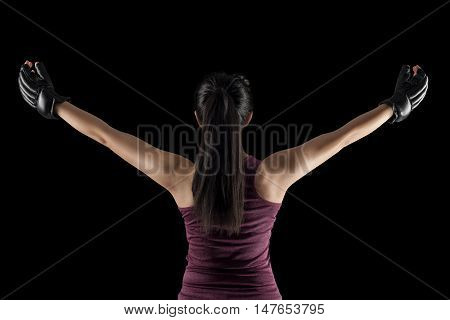 mma female fighter with hands raised up, view from the back, isolated on black background