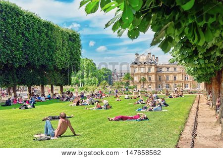 Paris, France - July 08, 2016 : Parisians And Tourists Have A Rest On The Lawn Near The Luxembourg P