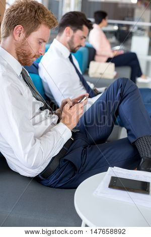 Young businessman wait airplane on airport in waiting room