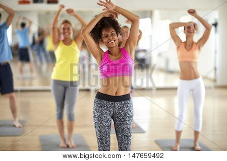 Happy girl dancing with young group in colorful sportswear in gym