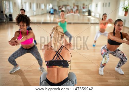Female blonde instructor with headset show squats and warming exercises to practitioners