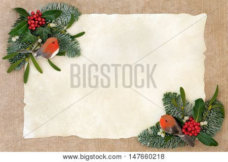 Winter and christmas abstract background border with robin decorations, holly, ivy, mistletoe, snow covered  fir and pine cones over old parchment and hemp paper.