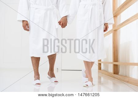 Enjoying each others company in spa. Close up of man holding woman hand and walking along spa center, wearing white robes