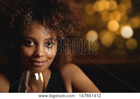 Close-up Portrait Of Smiling Black Woman With Healthy Skin Relaxing At Bar Counter, Holding Glass Of