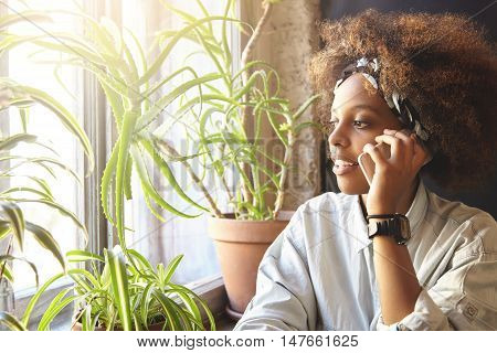 Cute African Female With Stylish Curly Haircut Having Nice Conversation With Her Friend Using Gadget