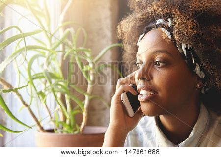 Indoor Shot Of Attractive Young Dark-skinned Woman, Using Cell Phone For Ordering Pizza For Dinner.