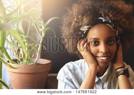 Happy Dark-skinned Student Girl With Afro Haircut And Ring In Her Nose, Wearing Bandana, Looking And