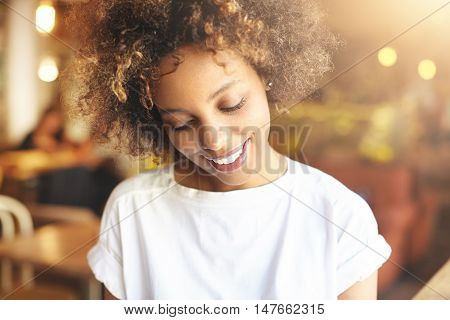 Good-looking African Woman With Afro Haircut Dressed In White Top, Enjoying Day-off At Cafeteria, Lo