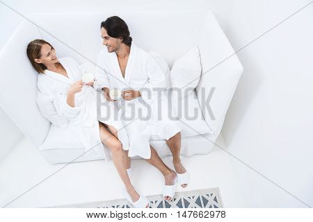 Taking load off at day spa. Shot of loving mature couple enjoying drink while relaxing together at day spa