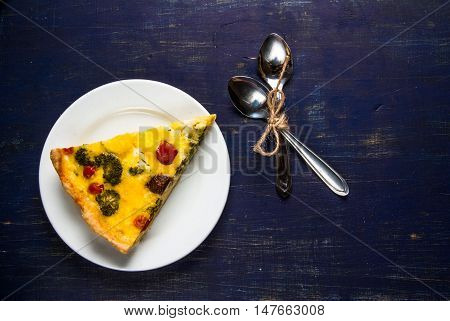 Slice of freshly baked homemade pie quiche lorraine on a dark blue wooden table, top view, copy space