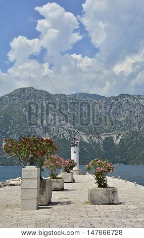 The artificially created island Our Lady of the Rock island in Kotor Bay Montenegro. Small oleander plants can be seen in the foreground and a small lighthouse in the background