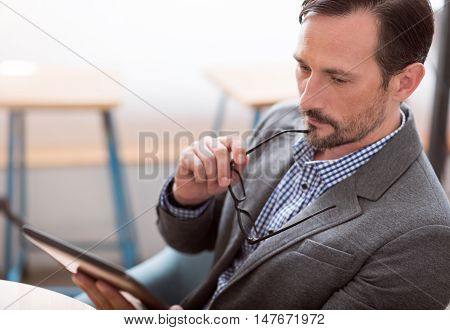 Seriously. Serious man using digital tablet while sitting at the table