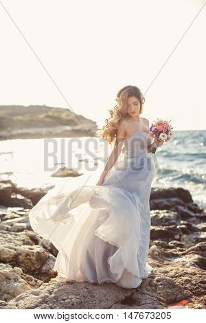 Beautiful young bride in long white wedding dress,off-shoulder beautiful long curly blonde hair,bride posing alone,standing on the rocky shore with a wedding bouquet of flowers on a background clear sky and blue ocean in the summer in the fresh air