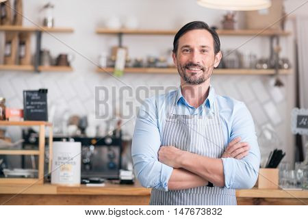 Own business. Successful cheerful small business owner standing with crossed arms