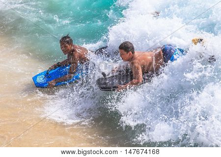 Waikiki Oahu Hawaii - August 27 2016: Little boys on vacation having fun swimming on boogie board at Waikiki Beach in Honolulu. The body boarding is the most popular water sports of Waikiki.