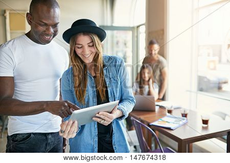 Handsome black man entering information on tablet computer held in front of him by young adult female in black hat in coffee house