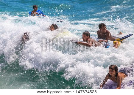 Waikiki Oahu Hawaii - August 27 2016: the funny and most popular water sports of Waikiki Beach in Honolulu: the boogie boarding or bodyboarding.