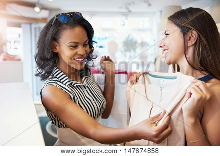 Smiling young women friends shopping for summer clothes together in a store holding up and examining a log sleeved top with happy smiles