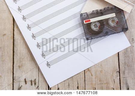 music paper, tape cassette on wooden table