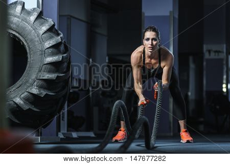 Concept: power strength healthy lifestyle sport. Powerful attractive muscular woman fitness trainer do battle workout with ropes at the gym