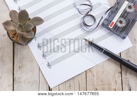music paper, cactus, fountain pen, tape cassette on wooden table