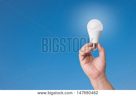 Hand Holding Led Bulb With Lighting On Blue Sky Background.