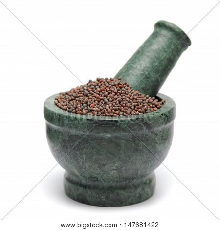 Organic Brown Mustard (Brassica juncea) on marble pestle. Isolated on white background.