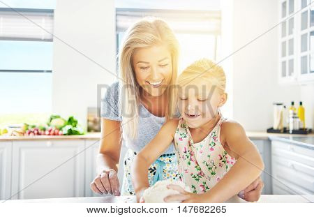 Adorable little girl kneading the dough watched over by her loving mother as she learns to bake high key sun flare background