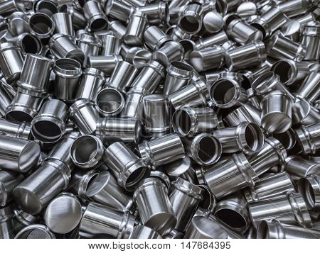 Shiny cold deformated cylindrical steel body parts selective focus  background