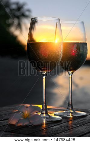Romantic beach scene: two glasses of red wine at sunset near water with sun beams