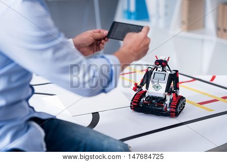 Great moment. Man's hands holding a camera to shoot a little cute robot