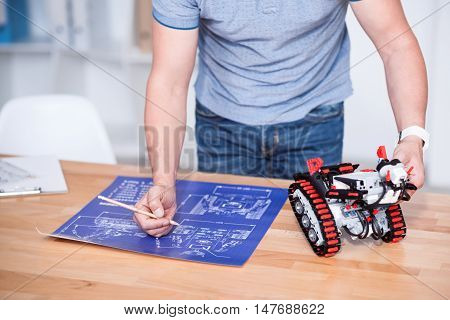Enticed in work. Pleasant professional engineer drawing a scheme and holding robot while working on the project