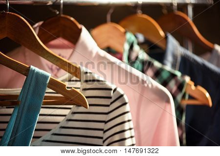Close up of female stylish clothes hanging on rack