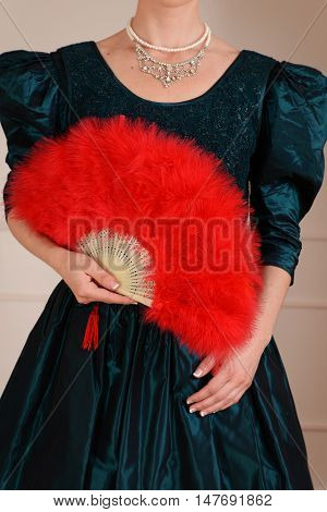 closeup Victorian woman holding red feather fan