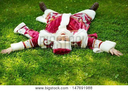 Santa claus man in Christmas new year red suit and hat lies on back on green grass on natural background
