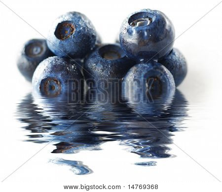 Blueberries over white background. Shallow depth of field. With reflection