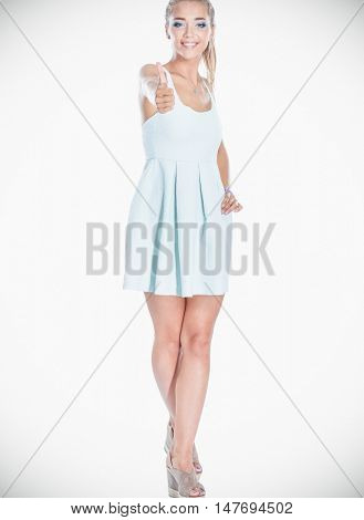 Pretty young woman wearing a nice summer dress, showing ok, isolated on white background
