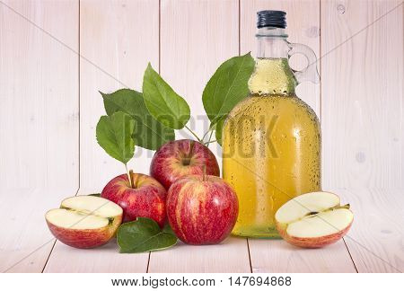 Cider and red apples with green leaves on wood background