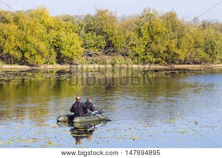 The river Chaus Kolyvan district Novosibirsk oblast, Siberia, Russia - September 17, 2016: fishermen in an inflatable rowing boat with a spinning rod looking for a predatory fish on the river.