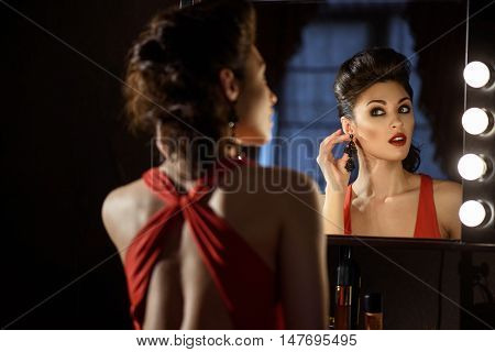 Seductive young woman preening before performance backstage. She is sitting near mirror and wearing earring with concentration
